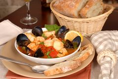 Bowl of delicious seafood soup with wine and rustic bread