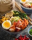 Spicy Noodle Lobster Bowl. A bowl of delicious spicy lobster noodles with soft boiled egg, carrots, baby bok choy, mushrooms, and grilled corn Stock Photography