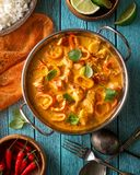 Thai Lobster Coconut Red Curry. A bowl of delicious Thai style coconut red curry with peppers, basil, lime and cilantro royalty free stock photo