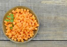 Bowl with diced carrots on wooden table. Closeup Stock Photos