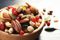 Bowl with different dried fruits and nuts on table. Closeup stock photo