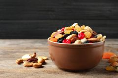 Bowl with different dried fruits and nuts on table. Space for text royalty free stock image