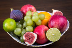 Bowl of different fruits. On wooden table royalty free stock images