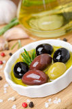 Bowl with different olives in oil, rosemary and spices Stock Image