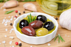 Bowl with different olives in olive oil and spices on wood Royalty Free Stock Photography