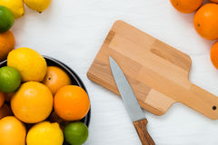 Bowl with different types of whole citruses: oranges, grapefruits, limes and lemons, and empty wooden board with a knife Royalty Free Stock Photography