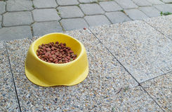 Bowl of dog food. RnYellow bowl of dog food on the floor royalty free stock images