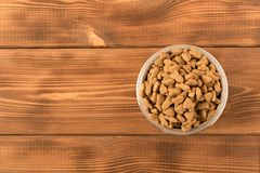 Bowl with dog food on a wooden table. Close up royalty free stock images