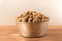 Bowl with dog food on a wooden table. Close up stock photos