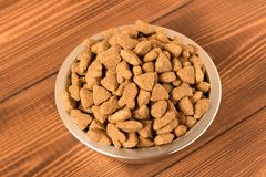 Bowl with dog food on a wooden table. Close up royalty free stock photography