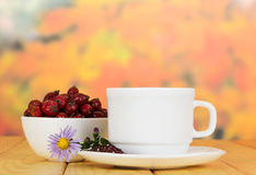 Bowl dog rose berries, cup tea on background autumn leaves. Royalty Free Stock Photos