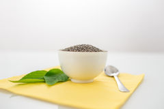 Bowl of dried chia seeds with fresh green leaves Royalty Free Stock Image
