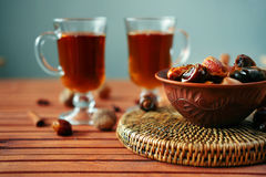 Bowl of dried dates on old wooden table with tea. Bowl of dried dates and other spices on old wooden table with tea in glasses Royalty Free Stock Image
