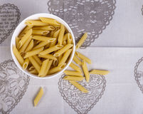 Bowl of dried penne pasta. White bowl of dried penne pasta Royalty Free Stock Images