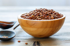 Dry brown lentils in a wooden bowl. Stock Images
