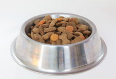 Bowl with dry dog food. A silver bowl filled with dry dog food royalty free stock images