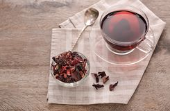 Bowl with dry hibiscus tea and cup of aromatic drink on wooden table stock photo