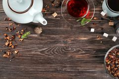 Bowl of dry hibiscus tea with fruits and cup of aromatic beverage on table royalty free stock images