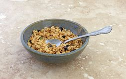 Bowl of dry organic breakfast cereal with dried blueberries and pumpkin seeds plus a spoon in the food. Side view of a bowl of dry organic breakfast cereal with royalty free stock photos
