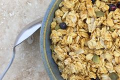 Bowl of dry organic breakfast cereal with dried blueberries and pumpkin seeds plus a spoon to the side. Top close view of a bowl of dry organic breakfast cereal royalty free stock photography