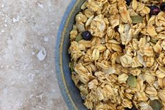 Bowl of dry organic breakfast cereal with dried blueberries and pumpkin seeds. Top close view of a bowl of dry organic breakfast cereal with dried blueberries royalty free stock images