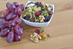 Bowl of dry seeds,nuts and red grapes on table. Healthy nuts, seeds and fresh red grapes  on wooden table with copy space Royalty Free Stock Photo