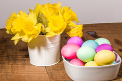 Bowl of dyed eggs with vase of flowers Stock Images