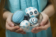 Bowl with Easter eggs in hands at the girl. The boiled decorated eggs for Easter in transparent dish, idea for children's creativity, are painted with paint of Royalty Free Stock Image