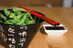 A bowl of EDAMAME. With chop sticks and soy sauce on the side Stock Photography