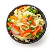 Bowl of egg noodles with vegetables. Isolated on white background, top view Royalty Free Stock Photos