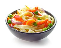 Bowl of egg noodles with vegetables. Isolated on white background, selective focus Royalty Free Stock Photos