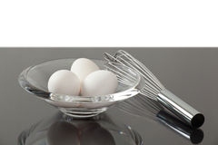 Bowl with eggs next to a whisk. On a counter Royalty Free Stock Photography