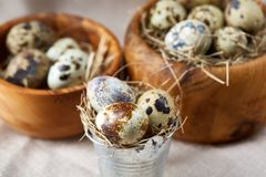 Bowl with eggs quail, eggs on a homespun napkin on grey background, close-up, selective focus. Wooden bowl with quail eggs, eggs on a homespun napkin on grey Royalty Free Stock Photography