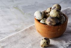 Bowl with eggs quail, eggs on a homespun napkin on grey background, close-up, selective focus. Wooden bowl with quail eggs, eggs on a homespun napkin on grey Royalty Free Stock Photo