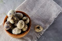 Bowl with eggs quail, eggs on a homespun napkin on grey background, close-up, selective focus. Wooden bowl with quail eggs, eggs on a homespun napkin on grey Royalty Free Stock Images
