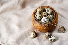 Bowl with eggs quail, eggs on a homespun napkin on grey background, close-up, selective focus. Wooden bowl with quail eggs, eggs on a homespun napkin on grey Stock Photos