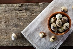 Bowl with eggs quail, eggs on a homespun napkin on wooden background, close-up, selective focus. Wooden bowl with quail eggs, eggs on a homespun napkin on piece Royalty Free Stock Images