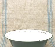 Bowl of enamel on linen sheet Royalty Free Stock Photos