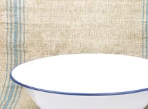 Bowl of enamel on linen sheet Stock Photo