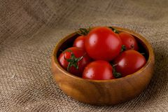 Bowl from exotic wood full of tomatoes Stock Photo