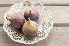 Bowl of figs on wooden table Stock Images