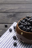 Bowl filled with bilberries, rustic style. Royalty Free Stock Photography