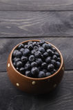 Bowl filled with bilberries, rustic style, vertical. Stock Photos