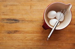 Bowl filled with eggs and whisk Royalty Free Stock Photography