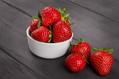 Bowl filled with fresh ripe red strawberries on wooden. Small white bowl filled with fresh ripe red strawberries on wooden table top Stock Images
