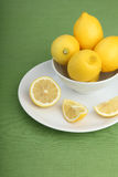 Bowl filled with lemons on green background Royalty Free Stock Photo