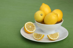 Bowl filled with lemons on green background Royalty Free Stock Images