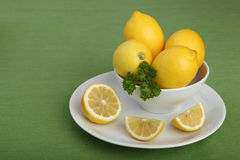Bowl filled with lemons and parsley on green background Stock Photography