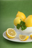 Bowl filled with lemons and parsley on green background Stock Images