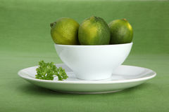 Bowl filled with limes and parsley on green background Stock Photo